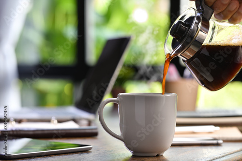 A hand pouring steaming coffee in to a cup on a work desk when work from home Fototapet