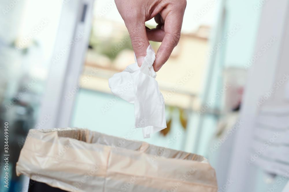 Fototapeta man throwing a used wet wipe to the trash bin