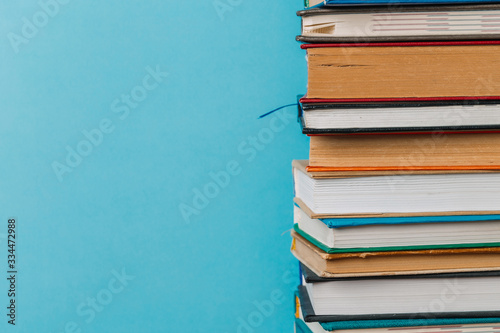 A simple composition of many hardback books, raw books on a wooden table and a bright blue background Wallpaper Mural