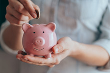 Female Hands Hold A Pink Piggy Bank And Puts A Coin There. The Concept Of Saving Money Or Savings, Investment