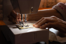 Sewing Machine And Old Grandmother's Hand In A Dark Room Sew