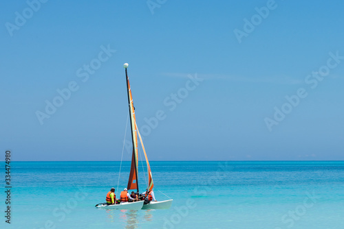Obraz na plátně a colorful and beautiful catamaran sails the turquoise blue waters with tourists