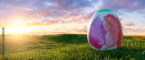 Fototapeta big painted colorful watercolor easter egg at easter on sunrise or sunset on a meadow landscape, Panoramic backgroud, with copyspace for your individual text. obraz