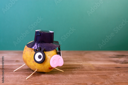 Photo Funny potato in the shape of a pig with a hat on his head