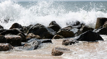 Ocean Waves Crashing On A Jetty Of Rocks On The Beach