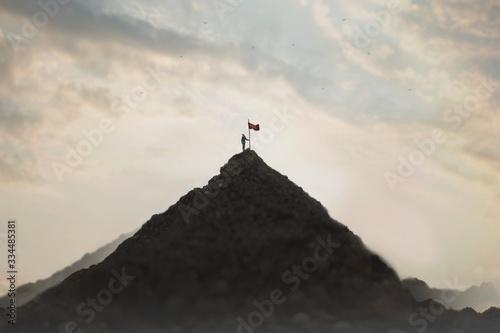 Fototapeta woman plants his flag on the mountain peak as a sign of success obraz