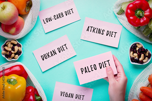 Foto Woman choosing between popular diets for weight loss with fresh fruits, nuts and vegetables in background