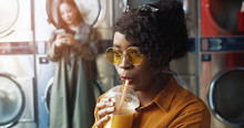 Close Up Of Pretty And Happy African American Girl In Yellow Glasses Drinking Orange Juice With Straw, Resting And Waiting For Clothes To Be Washed. Stylish Woman Sipping Drink In Laundry Service Room
