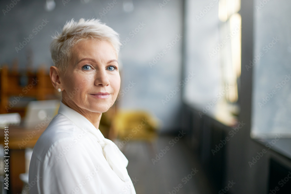 Fototapeta Isolated image of beautiful stylish middle aged female entrepreneur with neat make up going to business meeting, standing against office interior background, looking at camera with confident smile
