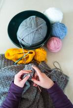 Woman's Hands Crochet Background.  Looking Down On Woman's Hands  Crocheting Blanket Out Of Light Blue Yarn