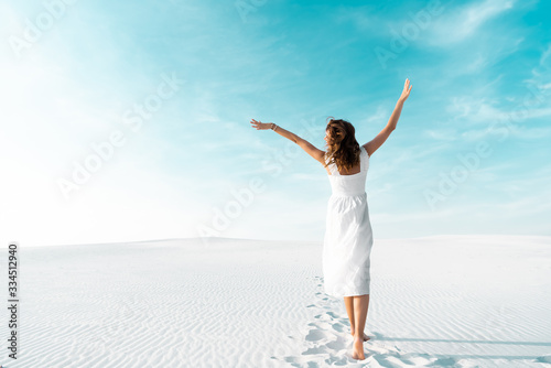 back view of beautiful girl in white dress with hands in air on sandy beach with Fototapete