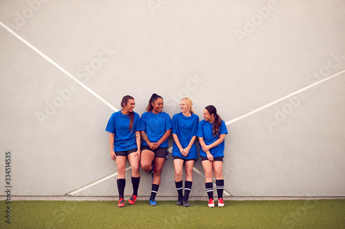 Fototapeta Graphic Shot Of Womens Football Team Leaning Against Wall Whilst Training For Soccer Match obraz