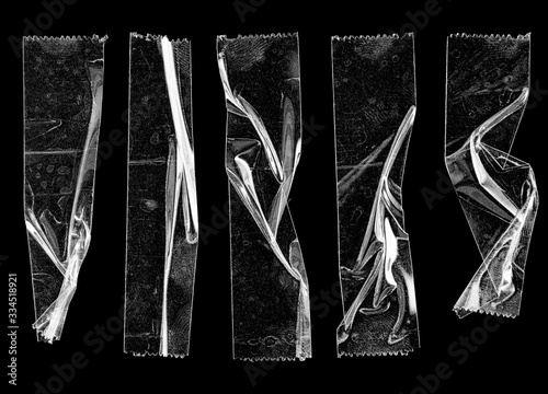 Fotomural set of transparent adhesive tape or strips isolated on black background, crumpled plastic sticky snips, poster design overlays or elements