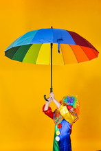 Clown Child In A Mask With A Large Colored Umbrella On A Yellow Background Creates A Festive Mood.