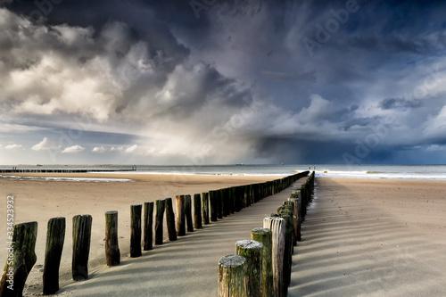 Fototapeta shower clouds over North sea beach obraz