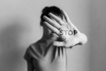 Stop domestic violence. The girl covers her face with her hand and asks for help. Domestic violence against women.