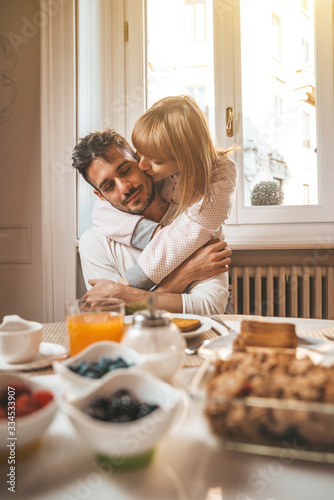 Fototapeta Couple in love eating breakfast early in the morning in the kitchen at home and having a good time. obraz
