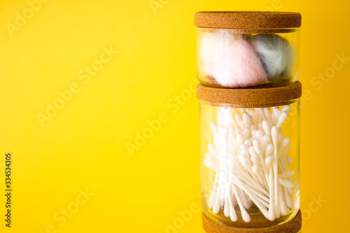 Photo cotton swabs, colored cotton wool ball inside glass small container with wooden top