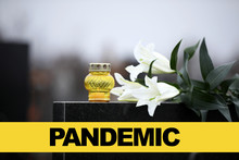 White Lilies And Candle On Black Granite Tombstone Outdoors. Outbreak Of Pandemic Disease