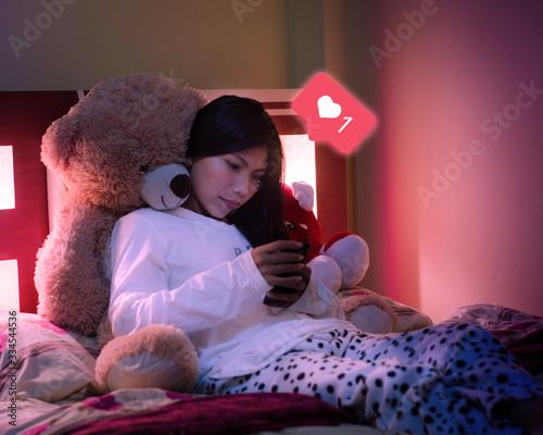 Photo mujer recostada en un oso en su cama peluche mirando su telefono redes sociales