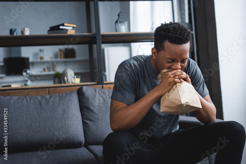 stressed african american man breathing with paper bag while having panic attack Canvas Print