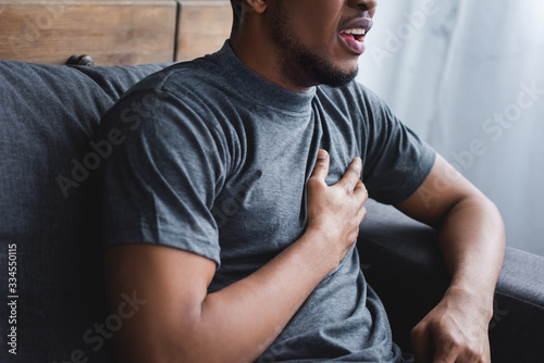 cropped view of stressed african american man having heart attack at home Canvas Print