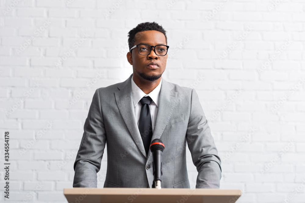 Fototapeta confident african american businessman having speech on tribune with microphone in conference hall