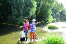 Little Boy Fly Fishing On A Lake With His Father And Grandfather. Man With His Son And Father On River Fishing With Fishing Rods. Fishing In River.