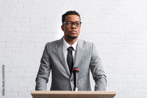Fototapeta confident african american businessman having speech on tribune with microphone in conference hall obraz