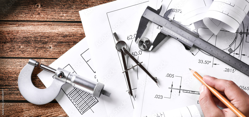 Fototapeta Engineer technicial drawings and mechanical parts engineering industry work project paper prints. Projectant hand with pencil, measuring tools on table.