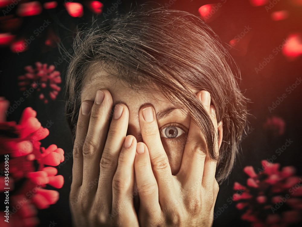 Fototapeta Concept of fear of coronavirus. Woman covers her face her hands on background with coronavirus.