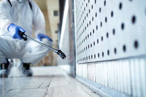 Fototapeta Shot of an unrecognizable person in white chemical protection suit doing disinfection of public areas to stop spreading highly contagious corona virus. Focus on sprayer nozzle. obraz