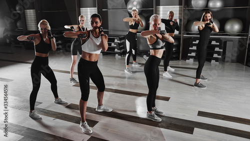 Women in black and white sportswear on a real group body Combat workout in the g Tablou Canvas
