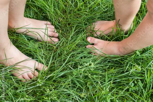 Fényképezés Two pairs of baby feet in green grass