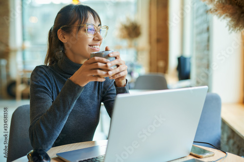 Obraz na płótnie Attractive smiling woman enjoying coffee while working in cafe or coworking space