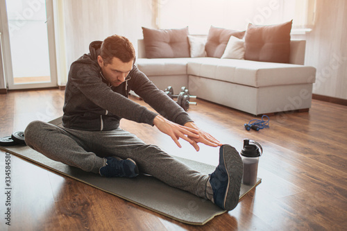 Young ordinary man go in for sport at home Wallpaper Mural