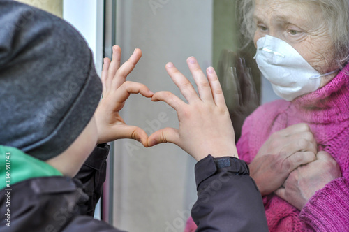 Foto Grandmother mature woman in a respiratory mask communicates with her grandchild through a window