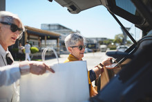 Senior Women Loading Shopping Bags Into Car In Sunny Parking Lot