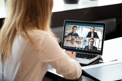 Back view of businesswoman speak using Webcam conference on laptop with diverse colleagues, female employee talk on video call with multiracial coworkers engaged in online briefing from home - 334591549
