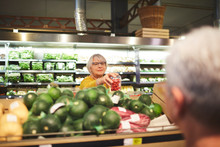 Senior Woman Shopping For Tomatoes In Supermarket Produce Section