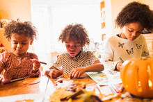 Brother And Sisters Making Autumn Crafts At Table