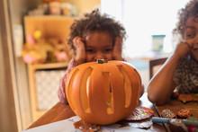 Portrait Cute Girl Carving Halloween Pumpkin At Table