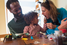 Happy Multiethnic Family Decorating Halloween Cupcakes At Table