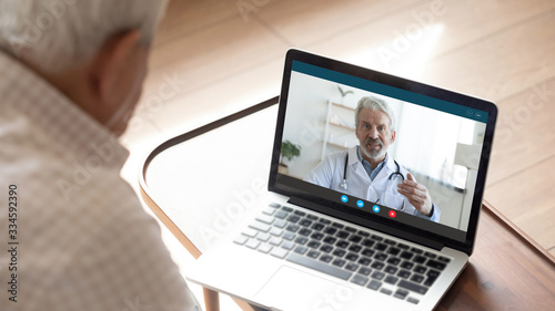 Back view of mature man have video call consultation with male doctor using laptop Webcam, close up of elderly male patient talk speak with GP or physician at home, discuss illness, consult online