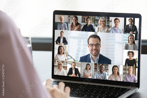 Fototapeta Close up of employee talk on video call on laptop with diverse colleagues, worke