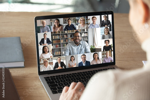 Canvas Print Back view of female employee speak talk on video call with diverse multiracial c