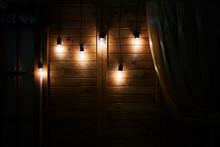 Old Light Bulbs On A Rustic Ba...