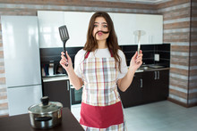 Young Woman On Kitchen During Quarantine. Hold Potato Masher And Kitchen Spatula Piece Of Hair As Moustache Between Nose And Lips. Have Fun Alone In Kitchen.