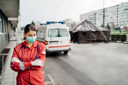 Fotografia Sad overworked paramedic in uniform  in front of isolation hospital facility