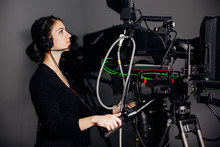 Recording Show At TV Studio.Professional Camera Operator With Camera In Television News Broadcast.Camerawoman Working With Big Positioned Broadcasting Video Camera.Reporting Crew